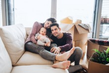 young family on couch with baby with moving boxes