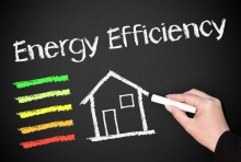 """A hand drawing """"energy efficient"""" and a house on a chalk board"""