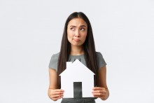 confused woman holding model house