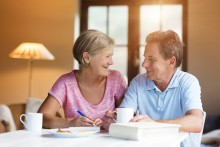 older couple planning bills over morning coffee at home