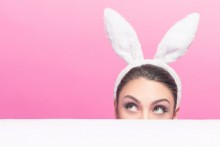 woman peeking over table with bunny ears on