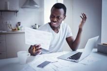 Man looking angrily at utility bill