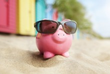 savings piggy bank on a beach with sunglasses, summer savings concept