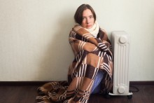 woman wrapped in a blanket, next to a radiator, looking cold