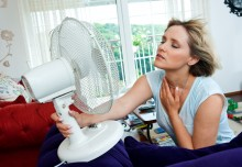 woman cooling off with fan at home