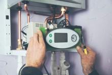 mans hands adjusting thermostat for a heating system