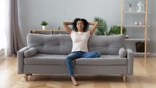 woman relaxing on couch in a clean house with plants