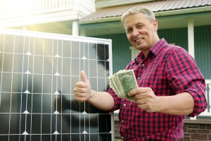 man giving thumbs up holding money next to solar panel