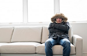 man in a winter coat angrily sitting on a couch
