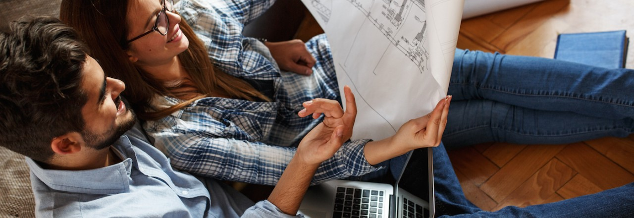 Couple sitting down with Laptop and blueprints planning out their next project