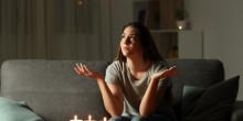 woman at home surrounded by lit candles because the power is out