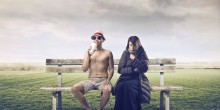 man in summer clothes sitting on bench next to woman in parka, changing seasons, hot cold concept