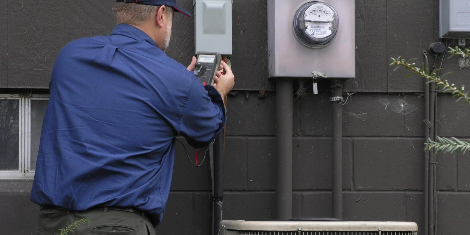 service technician maintaining air conditioning unit