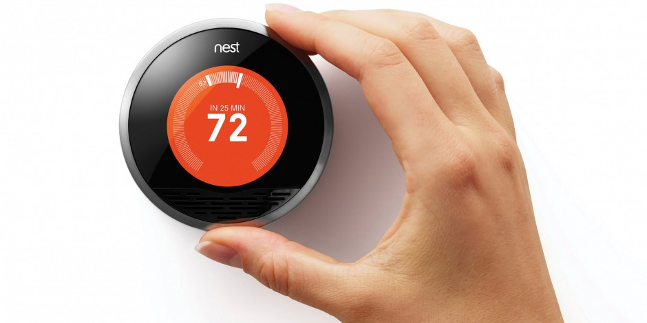 Nest Thermostat with hand adjusting the controls