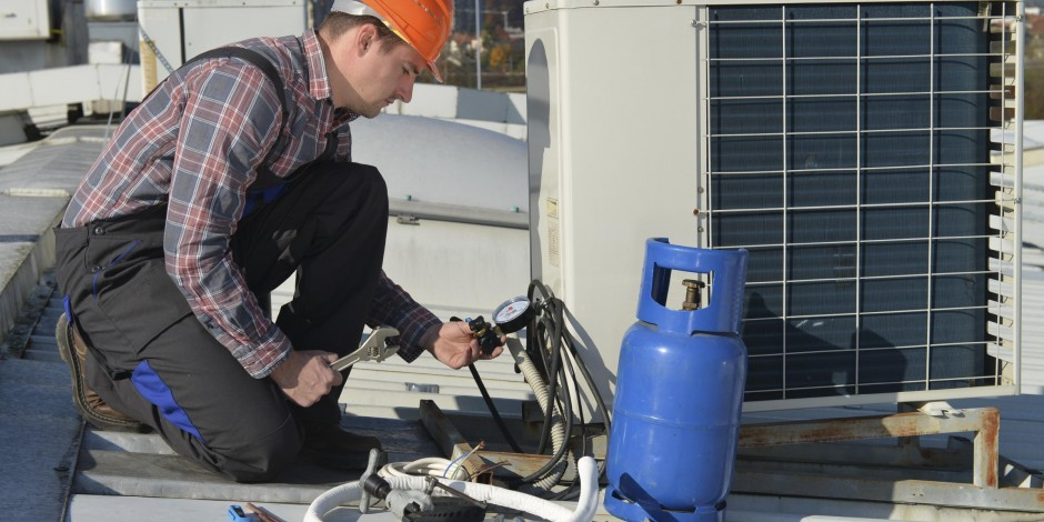 service technician working on roof unit of commercial building