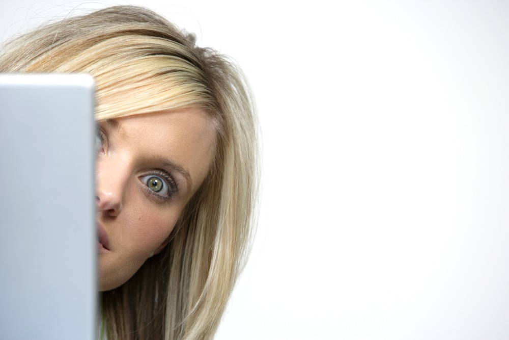 woman peeking around corner of laptop