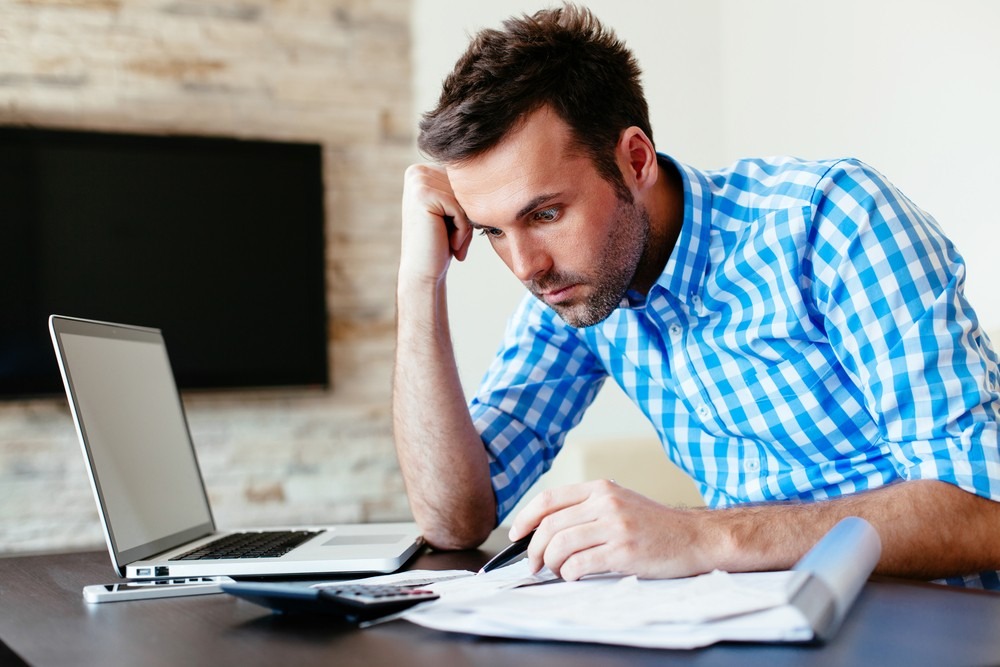 man worried and frustrated over utility bills