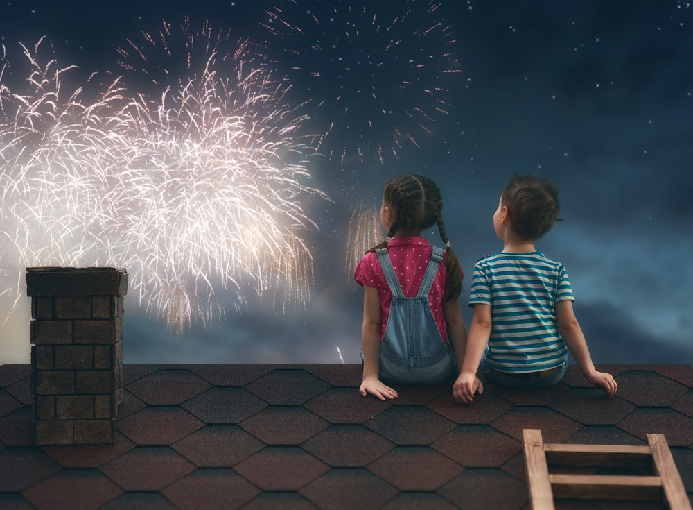 kids watching fireworks on top of home