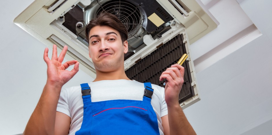 worker repairing ceiling air conditioning unit and giving an ok symbol with his hand