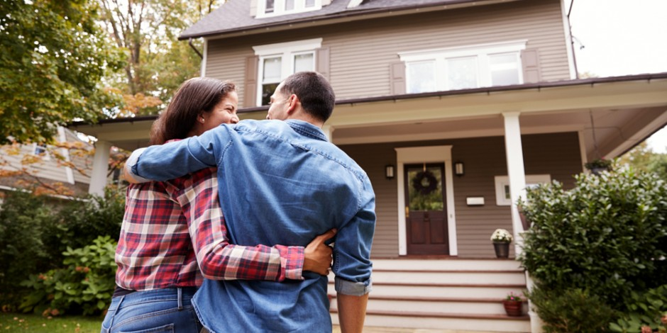 couple admiring home improvements outside front of house